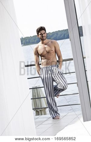 Full length of shirtless young man leaning on railing of hotel balcony