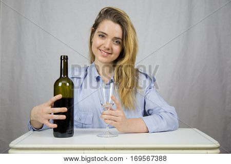 Young Caucasian white woman sitting at a table with a glass of wine in her hand and on the other a bottle of wine. She is blond and pretty with light brown eyes. The background of the image is white.