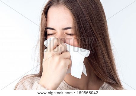 young girl with sniffles wipes the nose closeup in studio