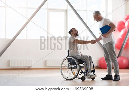 Nice to meet you. Happy positive smiling disabled man sitting in the wheelchair while shaking hands with his trainer