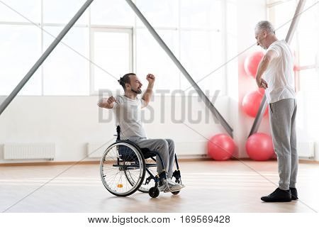 Repeat after me. Involved cheerful happy disabled man repeating exercises after the orthopedist and having a training session while expressing positivity and sitting in the wheelchair