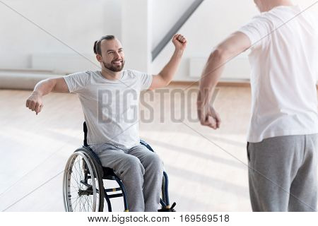 Physical therapy with my coach . Diligent cheerful smiling disabled man repeating exercises after the orthopedist while expressing positivity and sitting in the wheelchair
