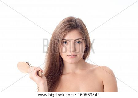 girl looks straight and holding a comb for hair closeup