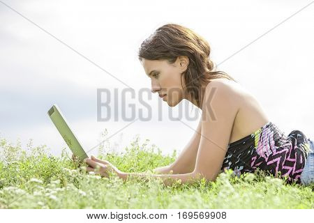 Side view of young woman using Tablet PC while lying on grass against sky