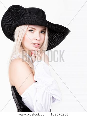 sexy woman with hourglass figure dressed in black leather corset with wide-brimmed hat.