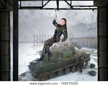 Girl soldier in training. Female soldiers hanging on the climbing equipment above the ground. At the bottom of the military vehicle tank soldiers