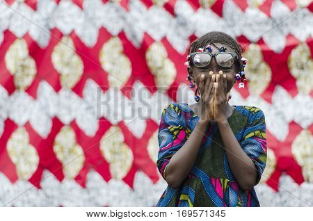 Young african girl with traditional accessories in hair hiding face and looking at camera