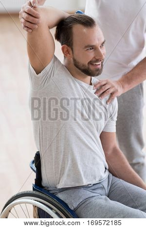 Full of positivity. Flexible joyful young disabled man holding the dumbbell and having the lesson with his coach while having the physical therapy session in the gym and expressing joyfulness