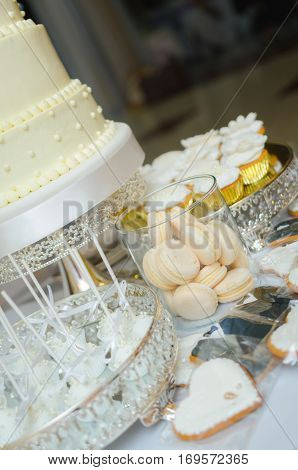 Delicious wedding candy bar table. Sweet holiday buffet with cupcakes, cakes and other sweet wedding desserts.