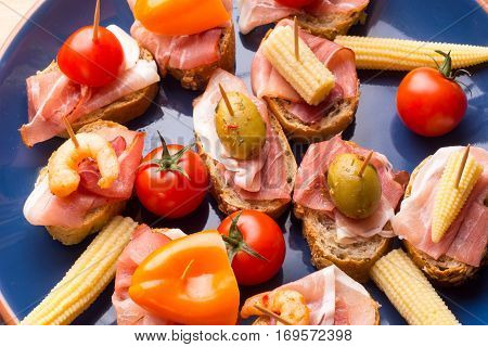 Set of Spanish sandwiches with ham olives and prawns - tapas on blue plate