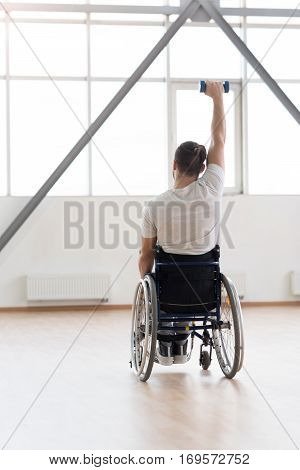Defeating the diagnosis. Athletic strong young invalid sitting in the wheelchair in the gym and looking at the window while exercising and holding the dumbbell and expressing positivity
