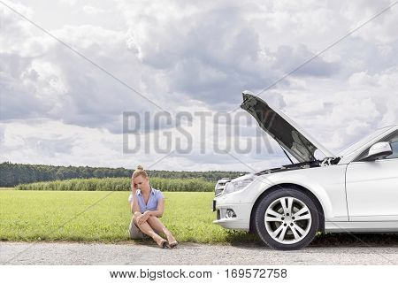 Full length of sad businesswoman sitting by broken down car at countryside