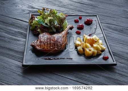 Roasted duck leg served on slate plate with apples and cherry sauce. Restaurant food on black wood table