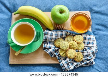 Breakfast served in bed - cup of green tea lemon cookies apple banana honey on a wooden board on background of blue denim bed linens. Tasty breakfast in bed concept.