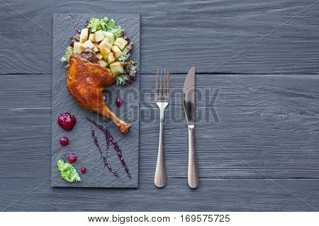 Roasted duck leg closeup served with apples and cherry sauce. Restaurant food on black square slate plate, top view with copy space on wood table background