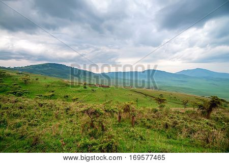 Scenic view in Tanzania with dramatic sky and small village ahead, depression near Ngorongoro crater