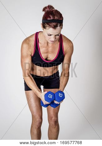 Beautiful strong muscular woman lifting dumbbell free weights in an indoor gym. Serious Female body builder doing bicep curls workout