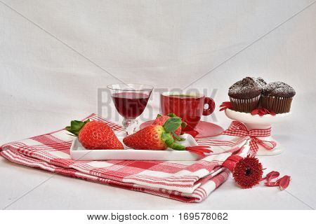 Chokolate mini muffins, espresso, coffee. Strawberries and liquor. flowerpetals. White linnen background. Tasty and Beautiful. Food and drink photo. Red Espresso cup.