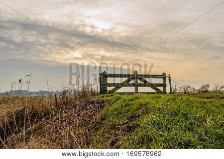 Closed wooden gate on top of Dutch dike as seen from the bottom on a cloudy day in the winter season.