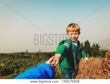 parent helping little son to climb in scenic mountains, helping hand concept