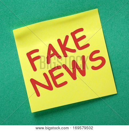 The words Fake News in red text on a yellow sticky note as a reminder to be aware of hoaxes and disinformation for propaganda uses