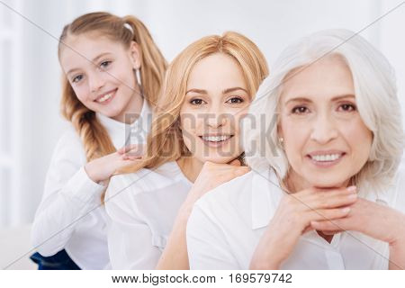 Family spirit. Cheerful delighted three generations of the family sitting on the cpuch and lookign at you while relaxing at home