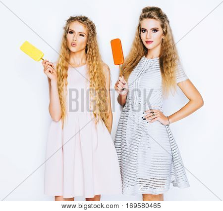 Two best friends girls having ice cream together indoor on yellow background. Gives a kiss. Close up of young women eating ice cream and having fun. Eskimo pie.