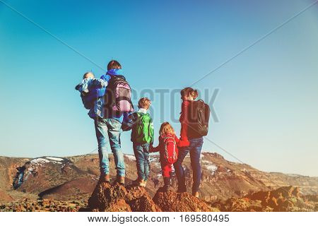 family with three kids hiking in mountains, family travel