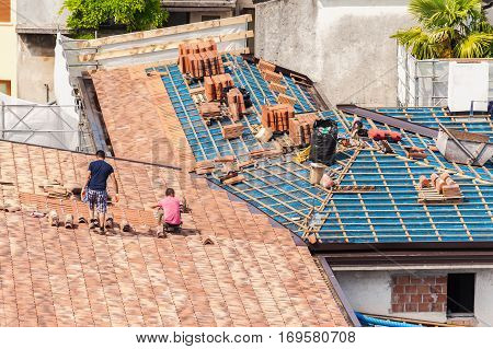 Construction site. Masons to work on the roof for laying tiles