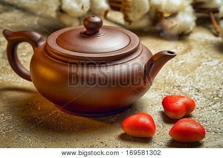 Brown ceramic kettle with three red marzipan in the shape of hearts. Still life on Valentine's Day.