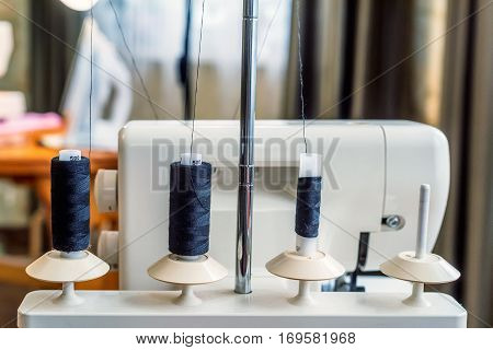 Professional overlock sewing machine with black thread rolls in workshop. Equipment for edging, hemming or seaming clothes at tailors shop