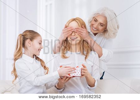 What a surprise. Cheerful content adult woman sitting on the couch while her mother and daughter congratulating her while going to celebrate at home