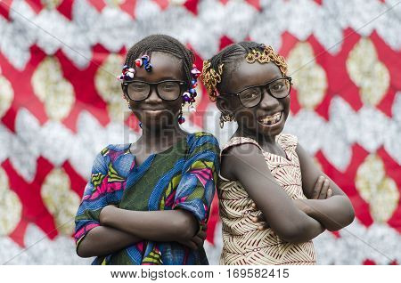 Young african girls with traditional accessories in hair standing back to back looking at camera