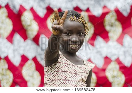 Young african girl with traditional accessories in hair doing victory sign and looking at camera