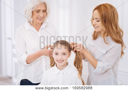 Nice hairstyle. Cheerful delighted girl expressing gladness while her mother and grandmother making ponytails