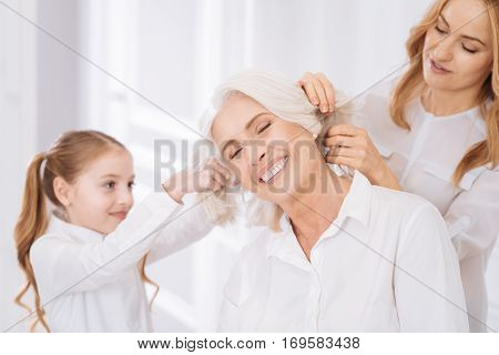 Time to play. Pleasant overjoyed aged woman smiling and having fun with her family why is playign with her hair