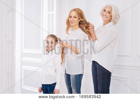 Three generations. Positive delighted caring family members making hairstyles for each other while having fun at home