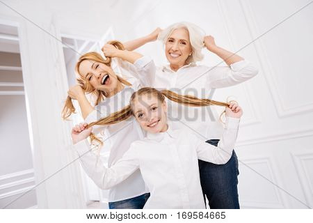 Rise your mood. Cheerful delighted three generations of the family playing with hair and smiling while enjoying fun together