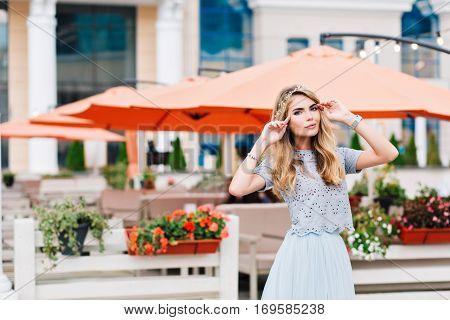Beautiful blonde girl in blue tulle skirt is walking on terrace background