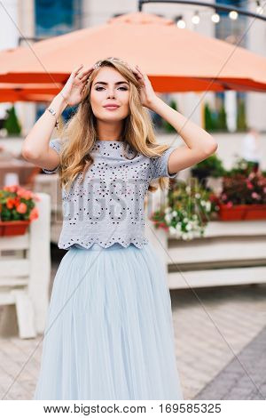 Cute girl with long blonde hair in blue tulle skirt is walking on terrace background
