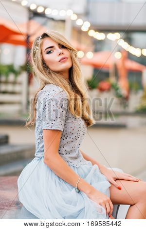 Attractive blonde girl in blue tulle skirt sitting on terrace background. She keeps hand on naked leg, looking to camera