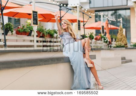 Attractive girl with long blonde hair in blue long tulle skirt having fun on terrace background. She keeps hand on leg and smiling to camera