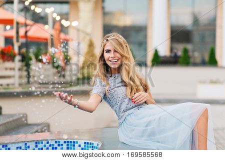 Pretty blonde girl in blue tulle skirt having fun on terrace background. She splashing water and smiling to camera