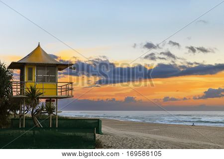 Life saver tower at sunrise on Gold Coast Surfers Paradise beach, with person sitting on the beach.