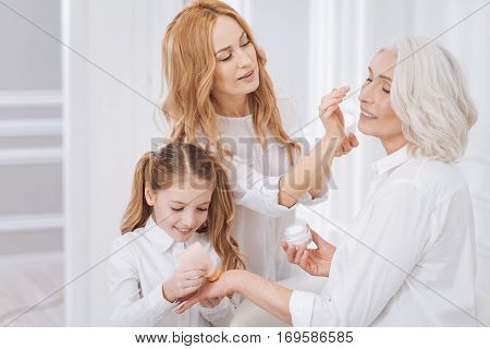 So beautiful and young. Cheerful beautiful aged woman smiling and resting with her family while enjoying beauty treatments