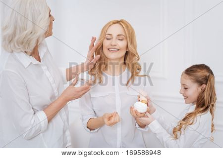 Enjoy every moment. Cheerful delighted attractive adult woman feeling happy and smiling while using beauty creams with her mother and little daughter