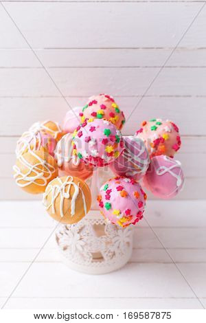 Cake pops on white wooden background. Selective focus. Place for text. Vertical image.