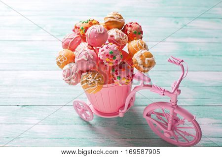 Bright cake pops in decorative bicycle on turquoise wooden background. Selective focus.