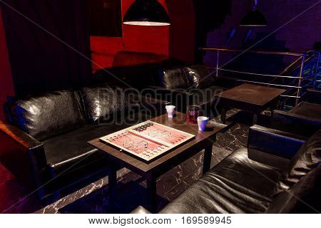 table with backgammon and tea in the cafe with dark subdued lighting for leisure with a modern design with red backlight
