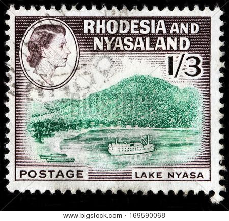 LUGA RUSSIA - SEPTEMBER 18 2015: A stamp printed by RHODESIA AND NYASALAND shows image portrait of Queen Elizabeth II against beautiful view of Nyasa Lake 1959